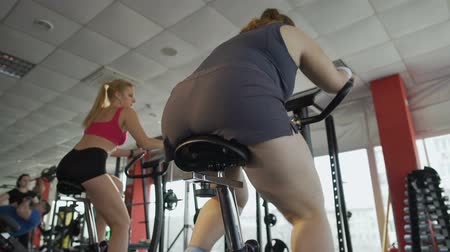 пухлый : Bottom view of obese female working at stationary bike in the sports club Стоковые видеозаписи