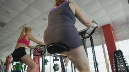 stationary : Woman with thick legs pedalling on stationary bike in the gym, weight loss