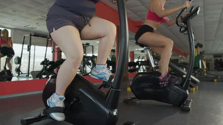 çabaları : Legs of obese female pedalling slowly at exercise bike in the fitness club Stok Video