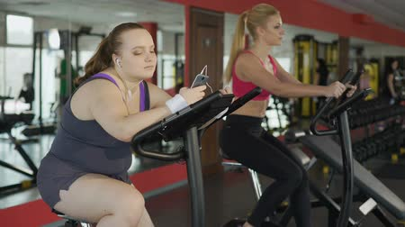 stationary : Lazy overweight woman riding sluggishly at exercise bike and scrolling on phone