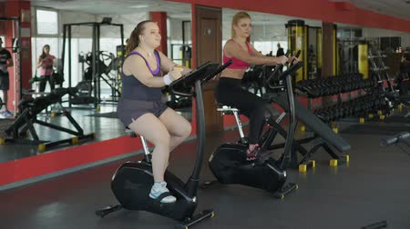 жирный : Lazy corpulent woman eating bun and riding at stationary bike in the gym
