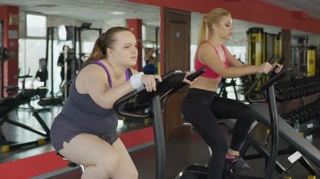 çabaları : Tired plump woman with stomach fat riding an stationary bike at last efforts Stok Video