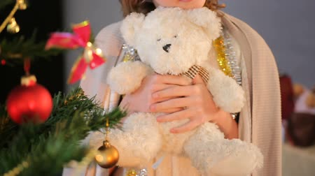 think big : Close-up of little girl standing near decorated fir tree and holding teddy bear