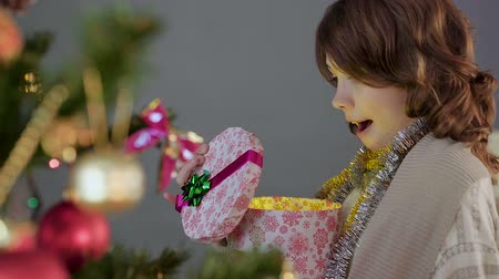 csőd : Little brunette girl opening Christmas present and smiling, miracle and magic