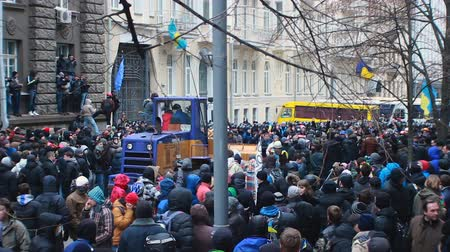 backwards : Big blue and yellow bulldozer moving backwards in middle of Ukrainian protesters