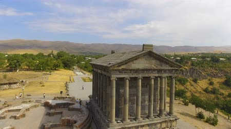 старомодный : Panoramic shot of old Garni temple overlooking mountains and village in Armenia