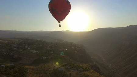 armenia : Red hot air balloon preparing for soft landing at mountain Armenian village Stock Footage