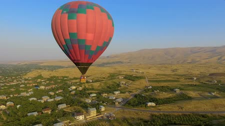 from air : Huge multicolored hot air balloon flying over Armenian village, landscape