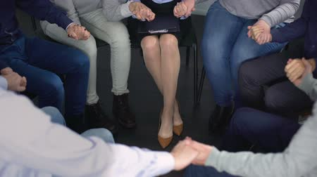 поддержка : Close-up of people sitting in circle and holding hands at therapy session