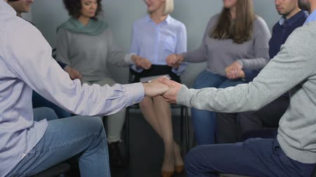 zihinsel : Group of colleagues sitting in circle and holding hands at team building session