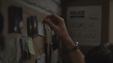 investigador : Concentrated detective marking criminal events on board with red string, links