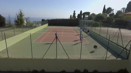 outdoor hobby : Aerial view of young people playing tennis, training before match, active hobby