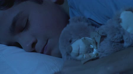 repousante : Soft dream of teenage boy hugging fluffy bear tor, lying on orthopedic mattress