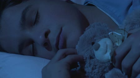 repousante : Sweet healthy dream of school boy cuddling teddy bear, comfortable mattress Stock Footage