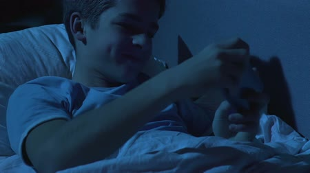 disobedient : Excited teenager playing game on smartphone lying in bed at night, discipline