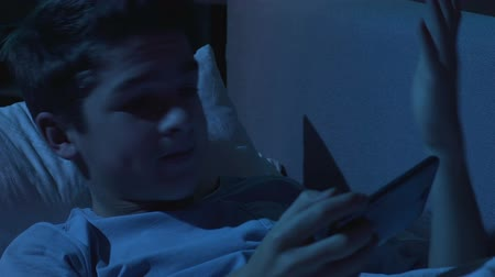 disobedient : Irritated teenage boy playing mobile game in bed sleeping time, loosing round