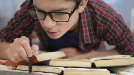 çivit : School boy reading interesting books, looking surprise, learning new information Stok Video