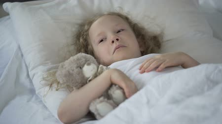 puericultura : Sad little girl with toy crying in bed, unhappy sick child feeling lonely