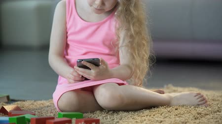 curly haired : Busy little girl using mobile gadget, playing games on smartphone, technology