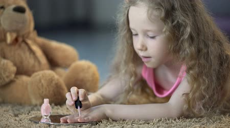 soon : Tender little girl painting nails with polish, kid dreaming to grow up soon Stock Footage