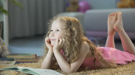 Пол : Cute curly-haired girl lying on soft carpet at home and smiling, happy child Стоковые видеозаписи