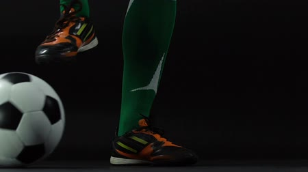 fotbalista : Soccer man legs with ball on dark background, kicker, preparation for the game
