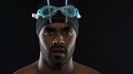 competitivo : Strong motivated swimmer putting on goggles, getting ready for competition