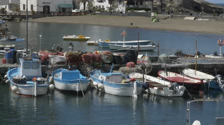 docked : Small bay with docked speedboats, fishing nets lying on mooring, seaside village Stock Footage
