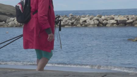 stepping : Female tourist with hiking poles in hand stepping down to seacoast, travel Stock Footage