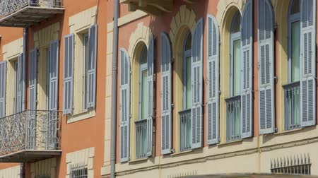 calçadão : NICE, FRANCE - CIRCA JUNE 2016: Buildings in the city. Residential complex windows and balconies shut on sunny day, urban architecture Stock Footage