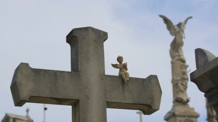 headstone : Old stone cross with little angel sculpture at Chateau Cemetery in Nice, France Stock Footage