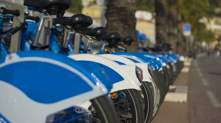 eco tourism : Blue eco-bicycles standing in row on street, bikes for hire, urban transport