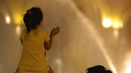 bofetada : Girl child clapping her hands, sitting on father shoulders, looking at fountain