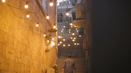 consumo : Man hurrying home, walking upstairs in narrow street illuminated with light bulb