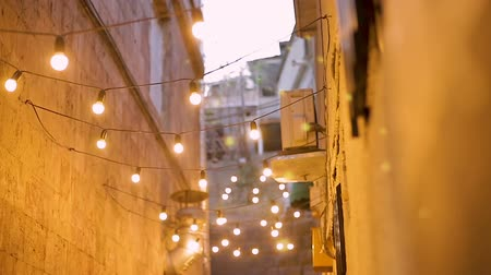consumo energia : Narrow street illuminated with light bulbs, festive mood in night city, design Filmati Stock