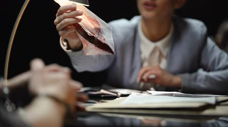 kajdanki : Female prosecutor showing knife with blood to suspect, waiting for confession