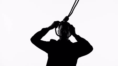 поражение : Silhouette of man putting loop on neck, going to commit suicide through hanging