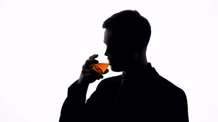 šik : Silhouette of business man sipping beverage, enjoying taste of aged whiskey