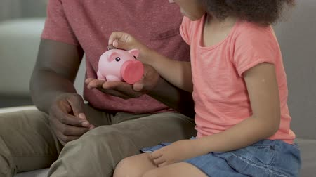копилку : Cute girl putting coin in piggy bank, father teaching child financial education Стоковые видеозаписи