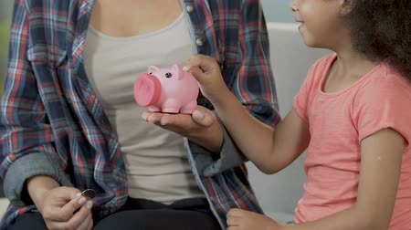 skarbonka : Mother and daughter putting coin in piggybank, financial responsibility, savings Wideo