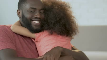 afro amerikan : African man hugging his cute daughter and smiling, parenthood, family comfort Stok Video