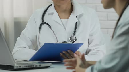 baca : Professional therapist keeping medical records, patient talking with doctor Stok Video