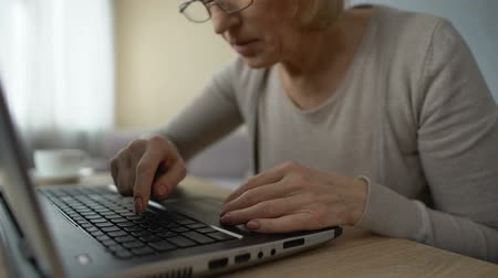 use computer : Old woman slowly typing on laptop at home, computer courses, online training