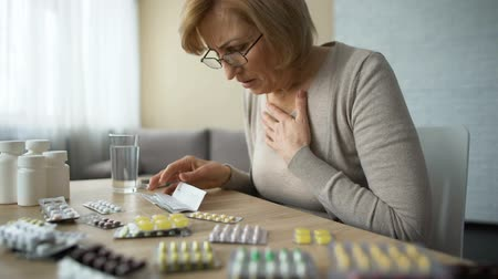 prescribe : Sad woman looking at table full of pills and sighs, old age disease, addiction