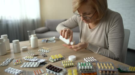 all ages : Senior woman taking capsules from all bottles, self-medication, pills addiction