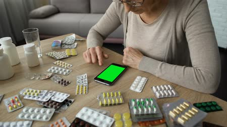 prescribe : Elderly woman scrolling smartphone, online medicine consulting, green screen