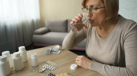 prescribe : Grandmother drinking prescribed pills for heartache, old lady suffering diabetes Stock Footage