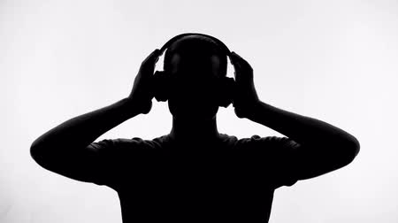 siluety : Man putting on headphones and listening to music, enjoying melody, inspiration