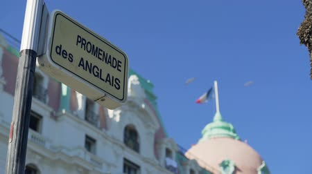 üç renkli : Promenade des Anglais street sign, French flag waving on top of building in Nice