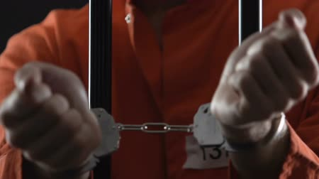 jail bars : Handcuffed killer signing police cooperation document and getting out of prison Stock Footage